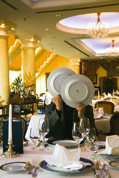 ein Herr sitzt in einem noblem Restaurant und versteckt sein Gesicht hinter zwei Tellern