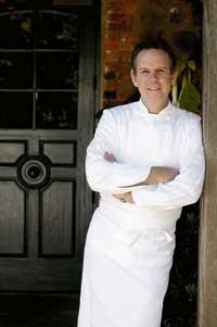 Thomas A. Keller lehnt im Kochgewand and eine Wand
