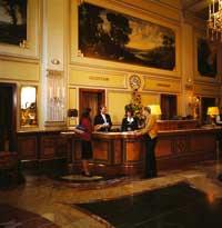 eine Dame und ein Herr stehen an der Rezeption des Hotels
