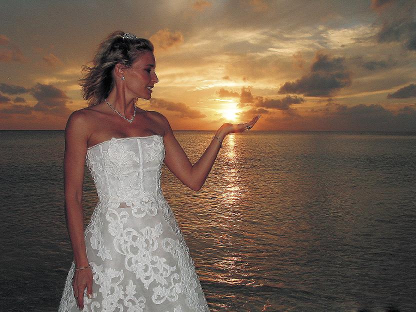 Eine Dame im Hochzeitskleid steht am Strand vor dem Sonnenuntergang und hält die Sonne in ihrer Handfläche