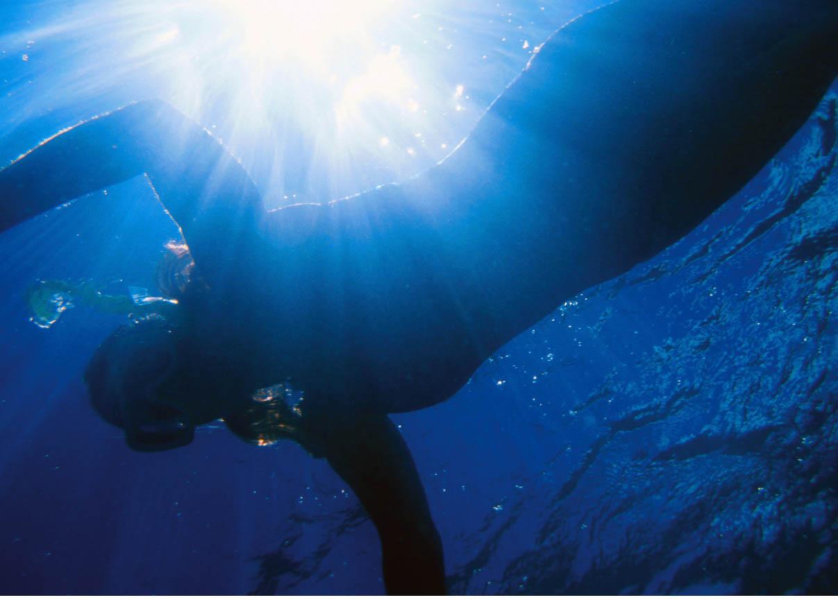 eine Frau schnorchelnd unter Wasser während die Sonne im Wasser reflektiert
