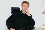 Mann gekleidet in Schwarz mit nachdenklichem Gesicht im Büro