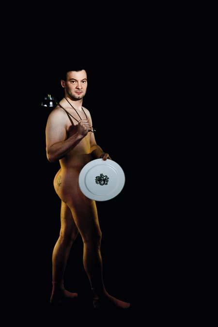 Didi Dorner nackt mit einem Teller bedeckt und einer Kelle über der Schulter