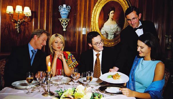 Zwei Paare beim festlich beim dinieren während der Kellner die Speisen bringt