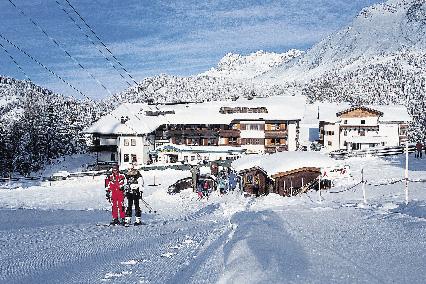 Hotel Hochgurgl im Winter bei Nacht mit zwei Skifahrern