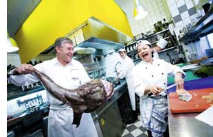 Christian Domschitz mit einem riesenfisch in der hand seine kollegin in der kueche damit aergernd