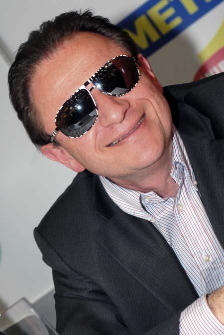 ein Brustbild eines Mannes im Anzug mit einer Sonnenbrille auf