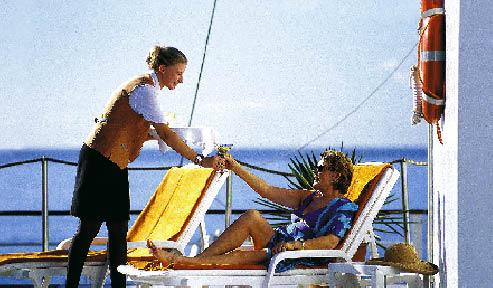 Eine Dame liegt auf deck eines Schiffs und lässt sich sonnen während ihr die Kellnerin ein Erfrischungsgetränk bringt