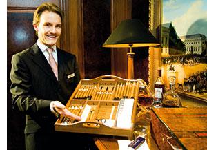 ein Mann mit einer Zigarrenbox, verschiedenste Sorten befinden sich darin