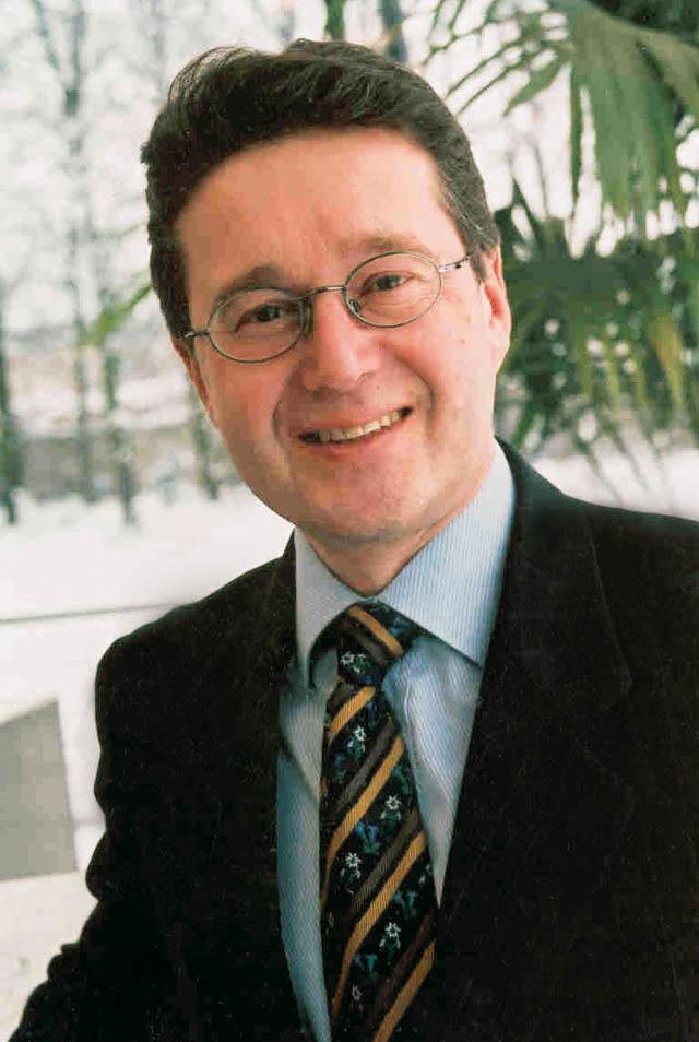 Mann mit Anzug und Brille lächenlnd
