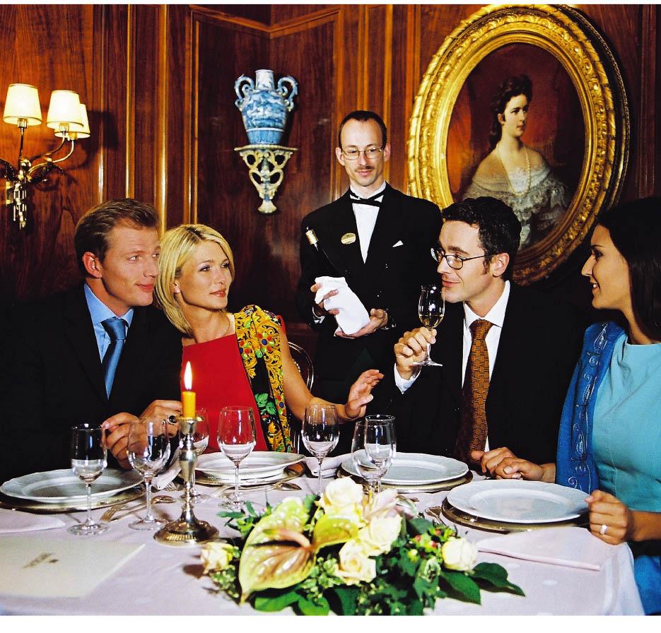 Ein Sommelier beratet einen Tisch mit zwei Paaren