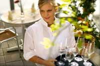 eine Kellnerin im weißen Hemd und einem Tablett mit Cocktails