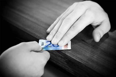 ein schwarzweisses bild, zwei haende die an endgegengesetzten enden einen zwanzig euro schein halten