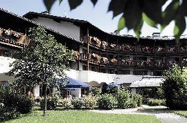 ein Hotel im Landhausstil mit einer Holzfront und Balkonen mit Blumen geschmückt