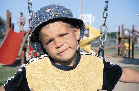ein kleiner Junge sitzt auf der Schaukel am Kinderspielplatz und sieht fragend in die Kamera