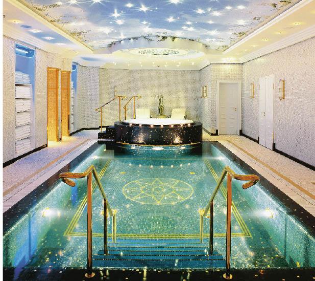 ein swimmingpool mit arabischen mosaiken verziehrt gefolgt von einem whirlpool