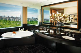 ein Einblick in ein Luxusbad, unter dem großen Fenster mit Blick auf den New Yorker Central Park steht eine Badewanne aus schwarzem Stein