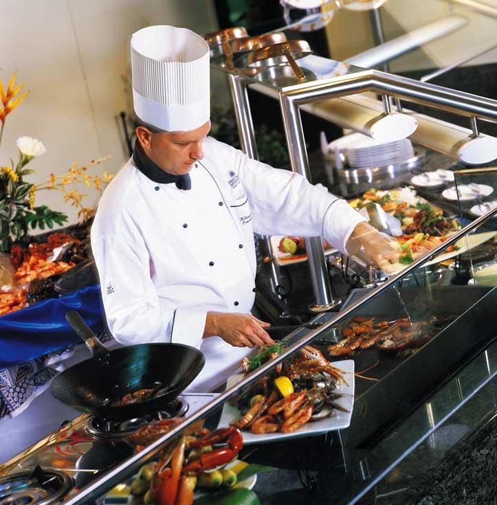 Ein Koch steht hinter einem Buffet mit diversen Köstlichkeiten