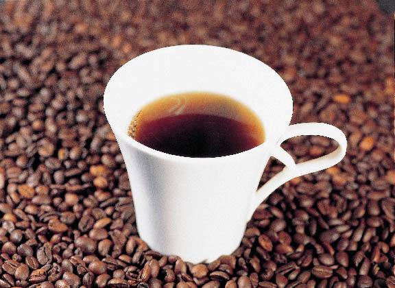 eine weiße Tasse gefüllt mit Kaffee plaziert auf Kaffeebohnen