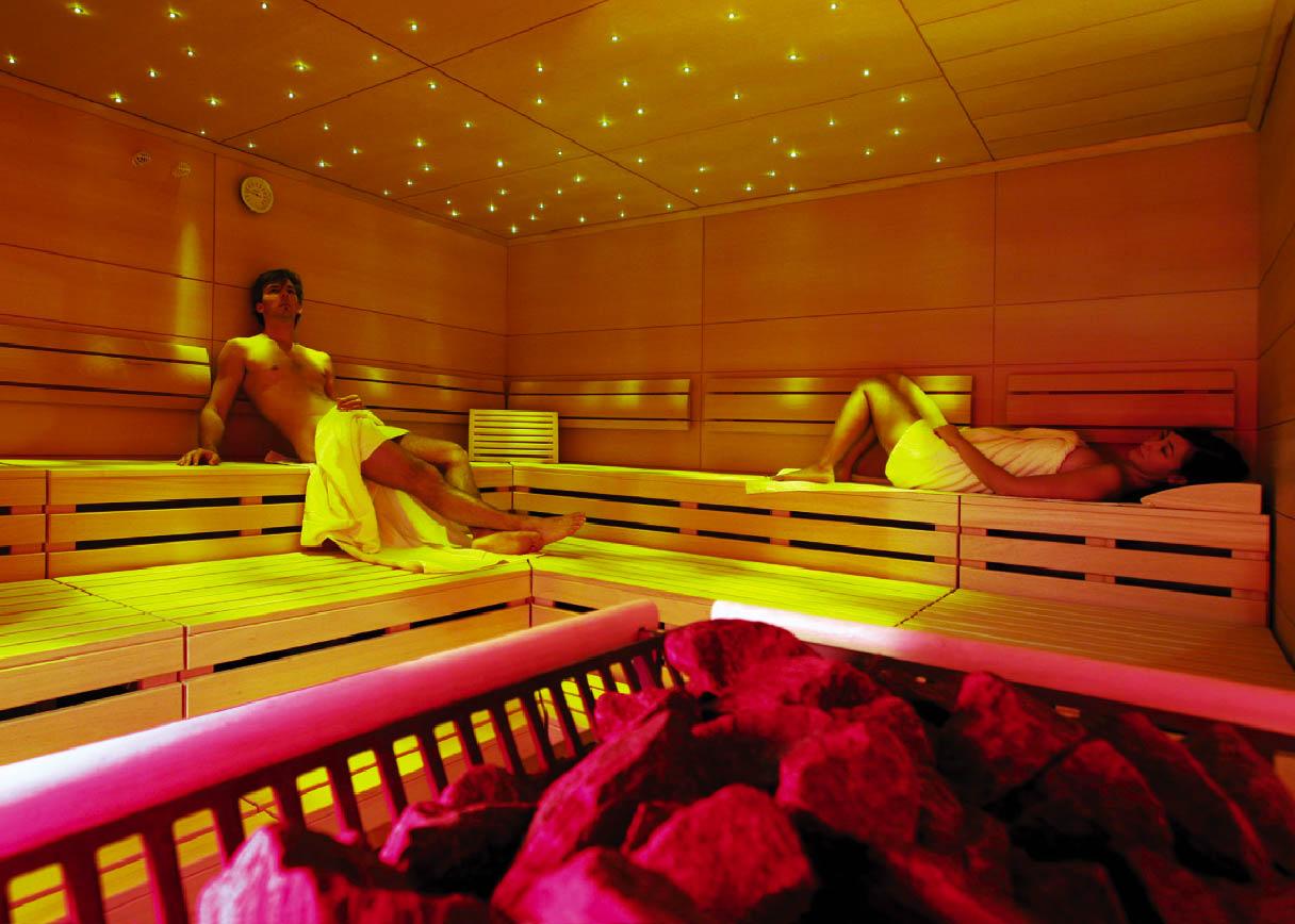 eine Dame und ein Herr liegen in der Sauna
