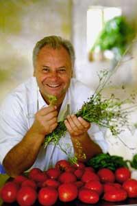 Eckart Witzigmann mit Kräutern in der Hand und vor ihm liegt eine Kiste Tomaten