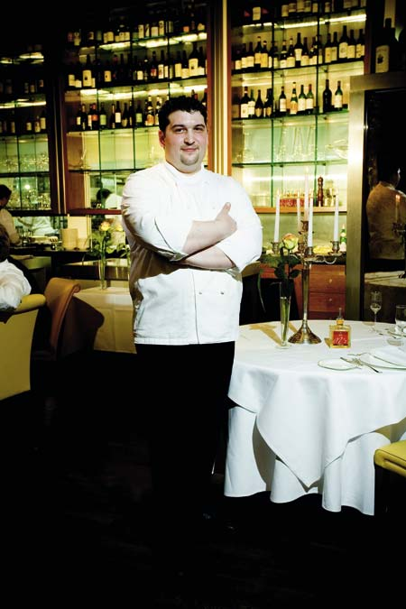 Starkoch Marco Pedrelli steht mit verschraenkten Armen in seinem Restaurant