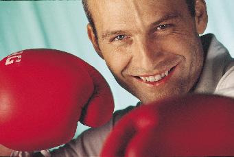 Ein Mann mit roten boxhandschuhen, in verteidungshaltung lächelt in die kamera