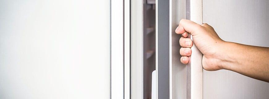 eine Hand greift an den Kühlschrank