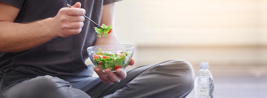 Mann isst eine Schüssel Salat