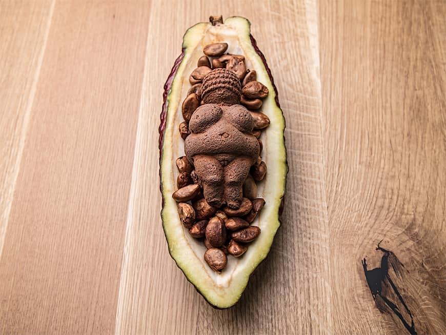 Schoko-Nougat-Mousse in Form der Venus von Willendorf mit Mispelkern-Ganache und eingelegten Mispeln