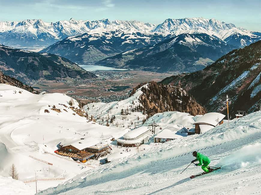 Ein Ski-Fahrer saust die Piste hinab, im Hintergrund schneebedeckte Gipfel