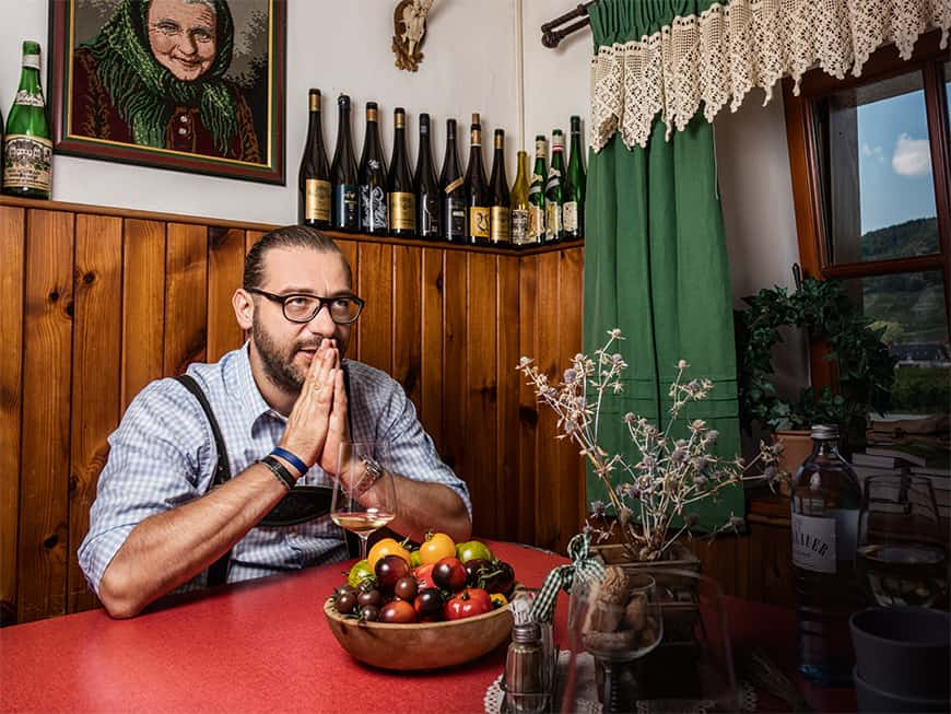 Bernd Pulker sitzt mit zusammengelegten Händen in seinem Heuriger und schaut nach oben.