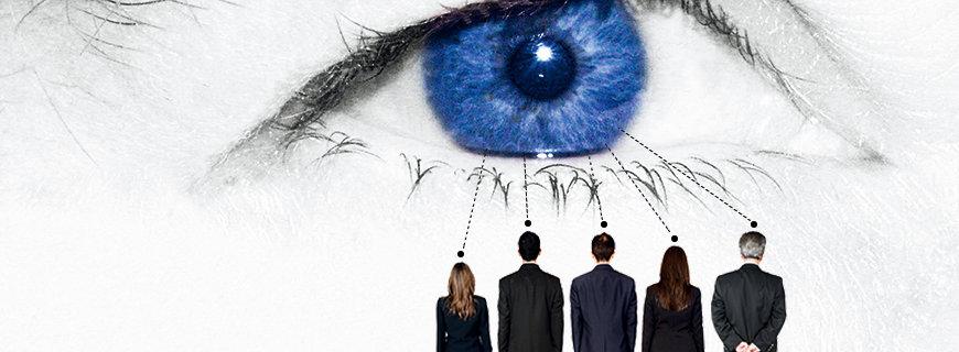 aufgereiht stehen Menschen die von einem übergrossem Auge in seinen Bann gezogen werden