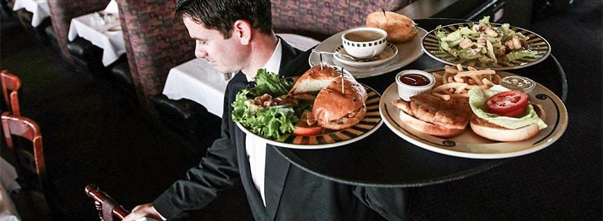 kellner serviert ein großes tablet mit drei teller. auf jedem ist ein burger mit salat und pommes