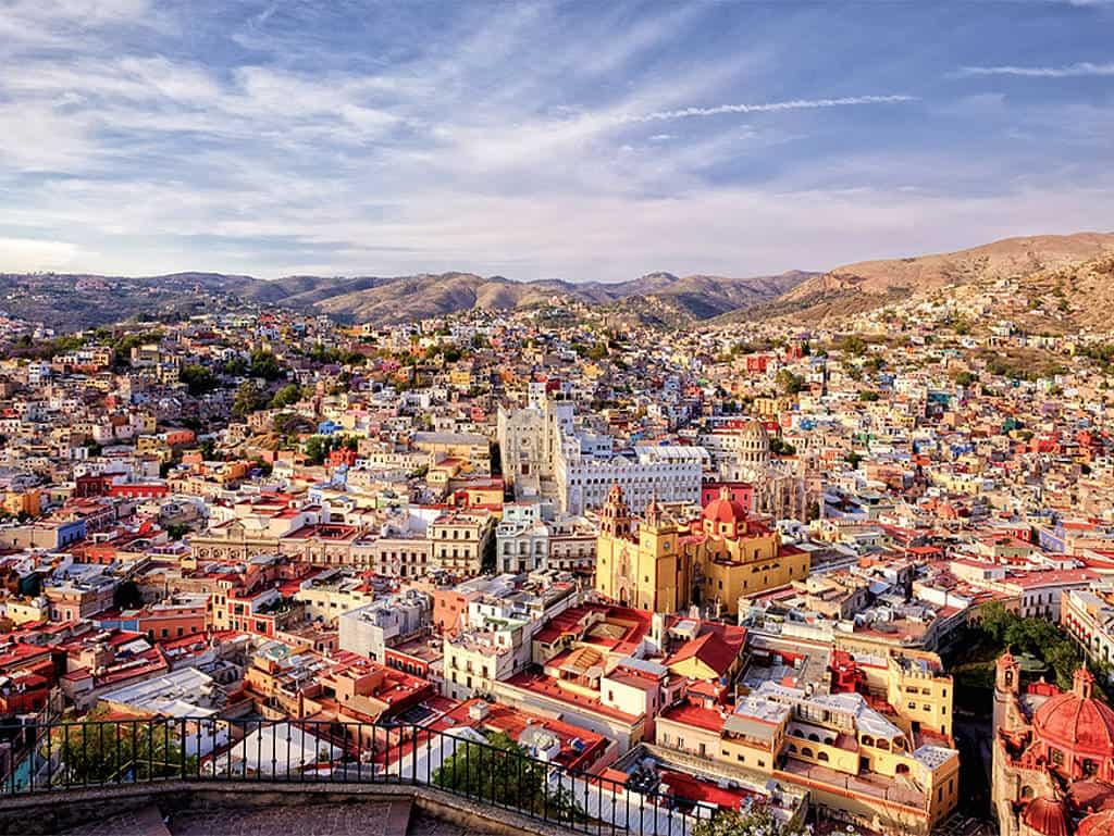 Blick über den Stadtkern mit bunten Häusern und Bergen im Hintergrund