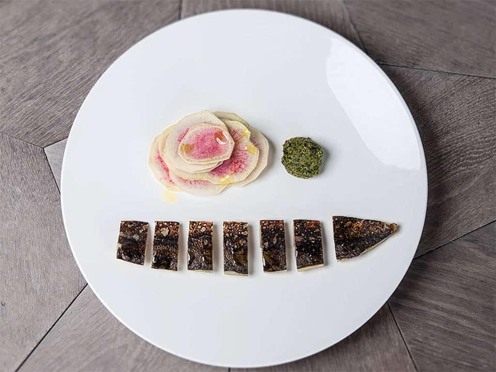 Gepökelte Makrele in Zentimeterstücke geschnitten und am weißen Teller angerichtet