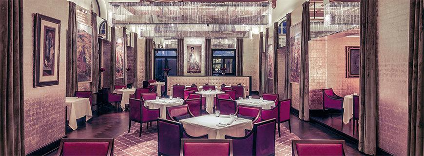 Interieur im The Restaurant: rote Stühle, Bilder an den Wänden und weiße Tischdecken