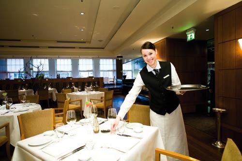 Kellnerin deckt die Tische des Restaurants für das Dinner