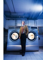 Ein Herr steht vor zwei Waschmaschinen