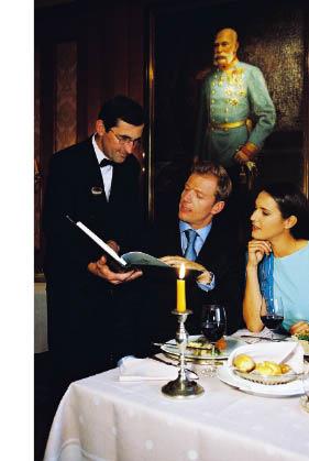 Ein Paar im Restaurant geht mit dem Kellner die Speisekarte durch