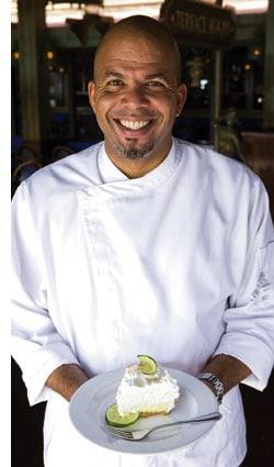 ein Koch mit einem Dessert in den Händen, grinsend über das ganze Gesicht