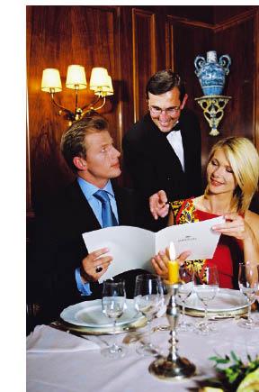Ein Paar bei einem romantischen Abendessen bei Kerzenschein wird vom Kellner beraten