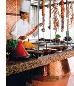 eine offene Kochstelle mit einem Koch voellig in seiner Arbeit vertieft