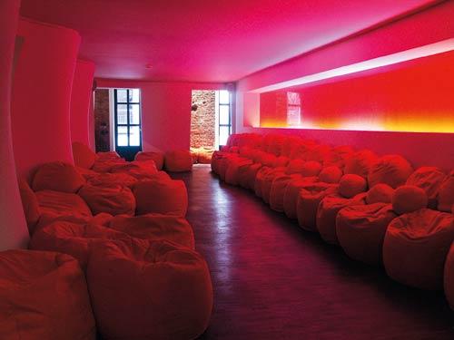 ein roter langer Raum gefüllt mit Sicksäcken