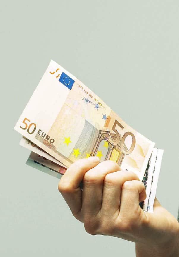 Eine Hand hält Bargeld, zu sehen ist ein fünfzig euro schein und mehr