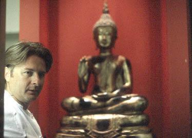 """""""Chef Extraordinaire"""" Wini Brugger mit einer Buddha Skulptur im Hintergrund"""