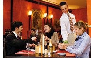 drei Menschen sitzen an einem Tisch, der Kellner bedient die Dame, die anderen beiden unterhalten sich angeregt