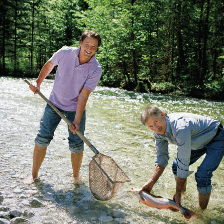 Andreas Döllerer und ein zweiter Mann im Fluss mit Netz am Fischen