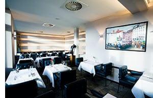 Schwarz-weiss gehaltens Restaurant, weisse eckige tische, schwarze Lederstühle