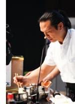 ein Meisterkoch arbeitet praeziese mit Essstaebchen
